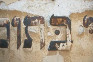 Nad hlavným vstupom je verš zo žalmu vzťahujúceho sa k Domu modlitby. Znaky sú kovové. Sú silne zkorodované. Farebnú úpravu sme neidentifikovali.