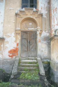 Štuková výzdoba portálu je realizovaná vo vápenno-cementovej omietke a je v dobrom stave. Omietka ľavého pilastra je deštruovaná a opadaná na murivo. Murivo je zvetrané.