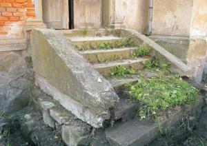 Vstupné schodisko má 7 stupňov. Stupne sú kamenné – pieskovcové. Zložené sú z kamenných blokov, ktorých maximálna veľkosť je cca 100 cm. Prvé dva stupne sú utopené v teréne. Bočnice schodov sú vymurované z kameňa a omietnuté tvrdou cementovou omietkou.