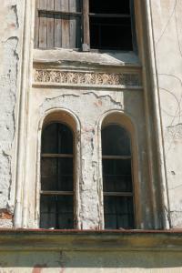 Deštrukcie omietkovej vrstvy v hornej časti fasády pod odkvapom. Sú dôsledkom havarijného stavu strechy a odkvapov v minulosti.