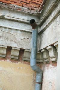 Detaily poškodení. Steny sú sekundárne pretreté okrovým náterom, štuková výzdoba bielym náterom. Náter pod korunou rímsou je zmytý a odhalená je primárna farebnos?ť fasády. Tmavočervená je plocha steny a biela je štuková výzdoba.