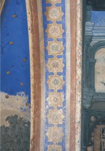 Výmaľba pásu steny medzi svätyňou a hlavnou sieňou je identická s výmaľbou pásu na speváckej empore. Šablónová výmaľba na okrajoch, na konvexnej profilácii, je silne zvetraná a chýbajúca. Zachovaná je fragmentárne. Na povrchu je silne znečistená depozitom.