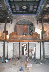 Pohľad na severozápadnú stenu so vstupom v prízemí a speváckou emporou na poschodí. Na podlahe prízemia je zachovaná dosková podlaha, na ktorej boli lavice.
