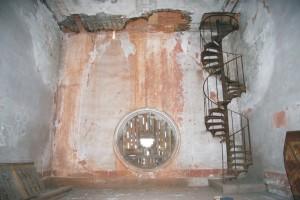 Pohľad na empory. Strop nad speváckou emporou je v dôsledku dlhodobého havarijného stavu strechy prehnitý a stena je viditeľne zatečená.